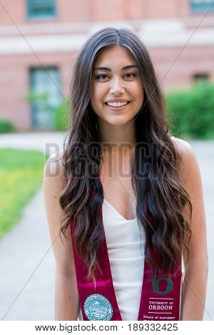 EUGENE, OR - MAY 22, 2017: College senior in natural light during graduation photos on campus at the University of Oregon in Eugene.