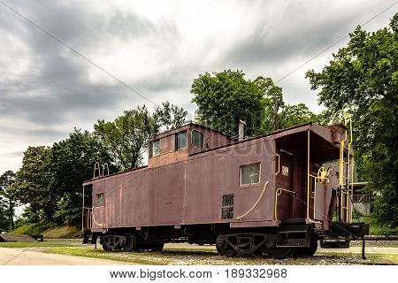 An old weathered train caboose on display
