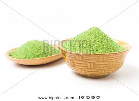 Green matcha tea powder in bowl white background