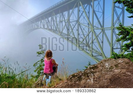 Woman meditating by ocean in foggy morning. Deception Pass Bridge Park. Seattle. Anacortes. Washington. United States.