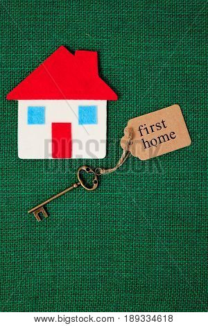 House with First Home key on green background