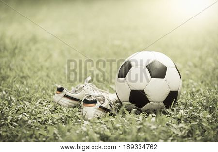 Football On Grass And Stud Shoe On Vintage Tone