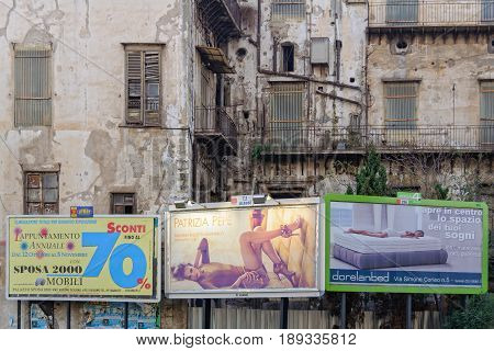 Illuminated billboards in front of a dilapidated house - Palermo Sicily Italy, 20 October 2011