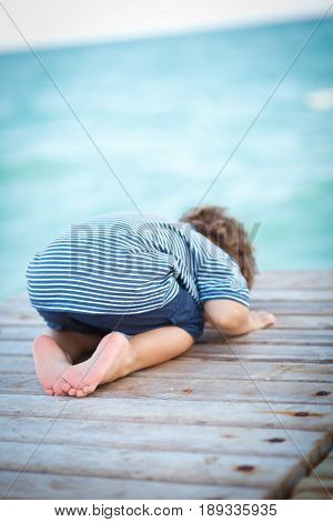 The boy bowed his head in the middle of the pier