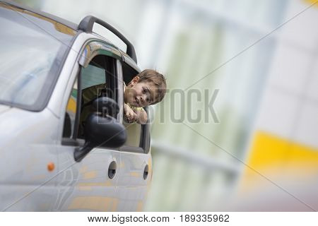 The boy looks out of the car window to hurry his parents and continue the trip