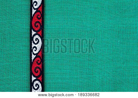 New Zealand - Maori theme - tribal design on green burlap background