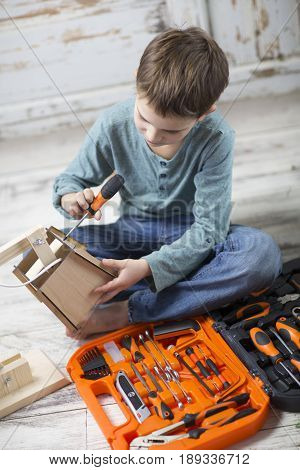 the boy opened the box with a hand tools and assemble on instructions a wooden table lamp