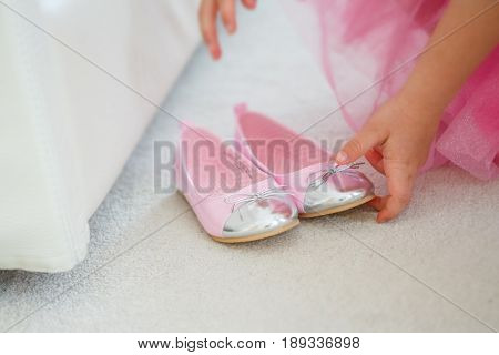 A little girl in a pink dress prepares to reconcile two shoes to the ball