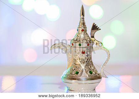 Silver Arabic Coffee pot  in colorful background. Ramadan, Eid concept