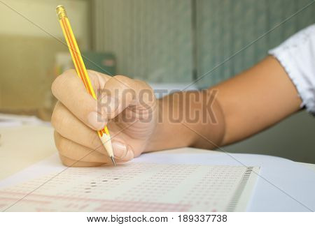 blurred of Asian Thai student testing in exercise exams answer sheets in university