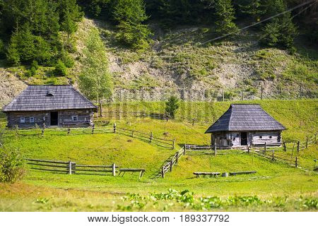 Two old wooden national houses in the Ukrainian Carpathian mountains in the summer