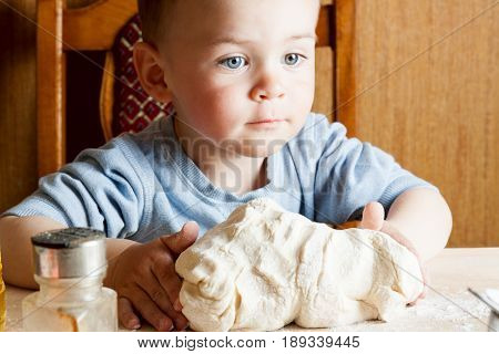 The Child On The Kitchen Kneads The Dough