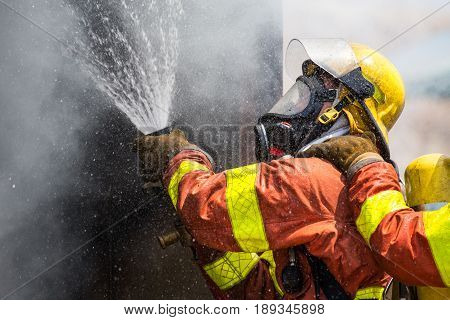 firefighter water spray by high pressure fire hose in smoke and droplets with copy space