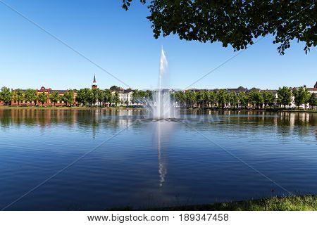 Fountain on the lake pfaffenteich in schwerin the capital city of mecklenburg-vorpommern germany blue water with reflection and blue sky copy space