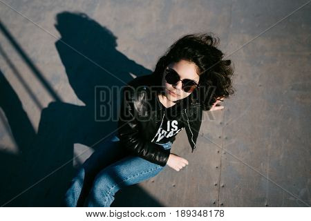 Pretty Girl With Curly Hair Resting In Skateboard Park. Portrait Of Beautiful Young Girl In The Skat