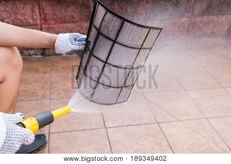 Person Spraying Water Onto Air Conditioner Filter To Clean Dust