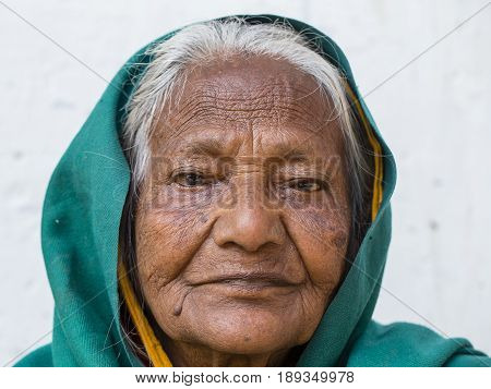 VARANASI INDIA - JANUARY 26 2017 : Portrait old beggar woman on street at Dashashwamedh Ghat in Varanasi Uttar Pradesh India