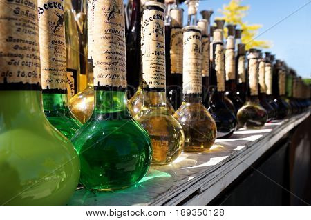 SCHWERIN GERMANY JUNE 2 2017: row of bottles with homemade green and golden wine liqueur and spirits on the street food festival market on a sunny weekend in the city