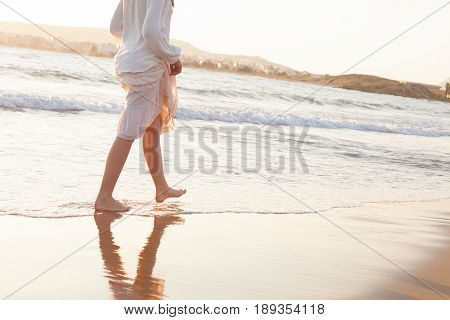 Female Legs Walking on Beach Vacation. Barefoot and Ocean Water on Summer Holiday Travel