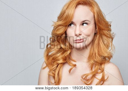 Headshot of doubtful Caucasian freckled female wearing nothingbut red long beautiful hair pouting lips and looking up with indecisive expression on her face showing doubt and hesitation. Body language.