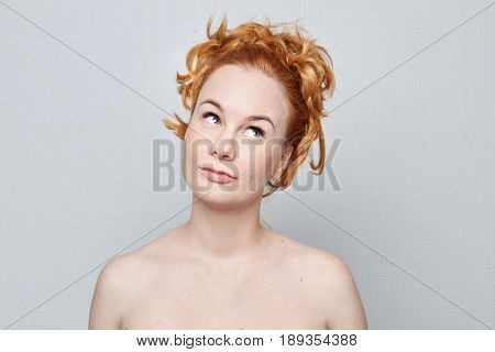 Human face expressions emotions and feelings.Nude studio portrait of beautiful young Caucasian redhead freckled woman looking playfully sideward demonstrating something on grey wall with copy advertising space.