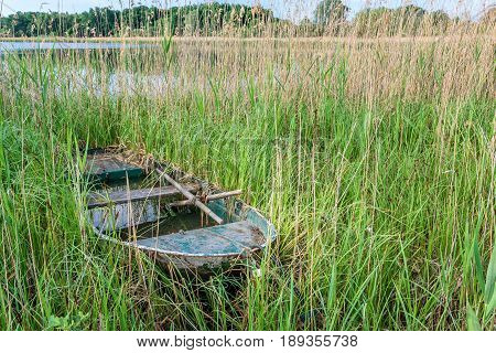 French countryside. An old wooden boat was forgotten on the banks in the reeds.