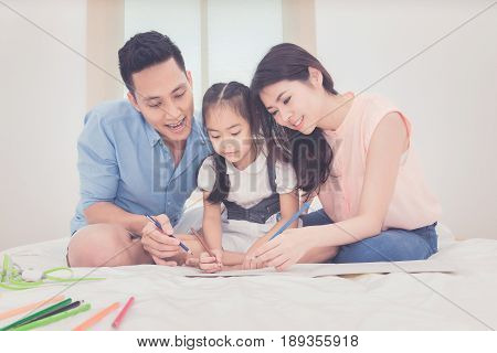 Happy Family In The Bedroom,asian Father And Mother Teaching Her Daughter Child To Studying At Home.