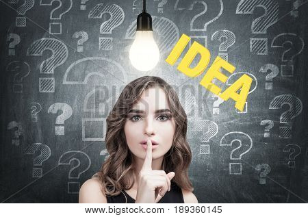 Close up of a young European woman with wavy hair making a hush sign. Blackboard background with an idea sketch on it and a light bulb on a wire above her head.