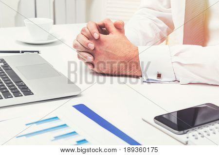 Close up of unrecognisable businessman s hands lying on his table with a smartphone a laptop and blue graphs attached to a clipboard. Toned image