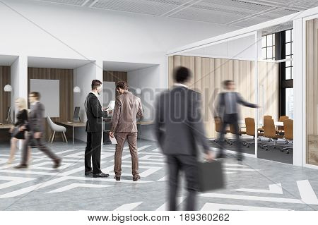 People near office cubicles in an office with white and wooden walls. There are blank vertical pictures in each of them a desk with a computer a chair and shelves. Side view. 3d rendering