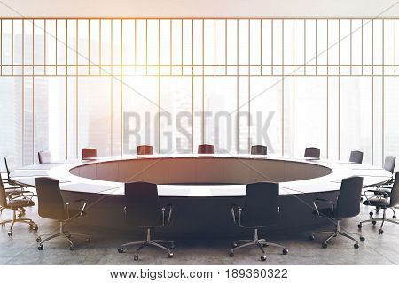 Meeting room interior with a large black round table office chairs standing around it and a window with a magnificent view. 3d rendering mock up toned image