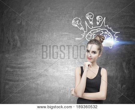 Portrait of a beautiful and pensive young woman wearing a black tank top. Her hair is in a bun. She is thinking and half smiling. Blackboard background with a brain sketch and light bulbs. Mock up
