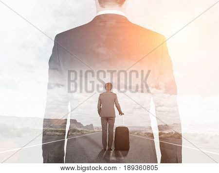 Rear view of a young businessman with a suitcase walking a lonely road. A larger businessman is following him. Mock up toned image double exposure.