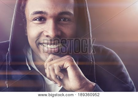 Close up of a cheerful African American young man wearing a T shirt and a hoodie and smiling. Toned image