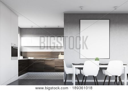 Front view of a gray kitchen interior with a poster hanging above a table with four chairs. Dark wooden countertops are seen in the background. 3d rendering mock up