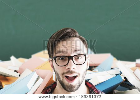 Close up of a surprised bearded man wearing glasses standing near a green chalkboard with piles of book behind him. Mock up