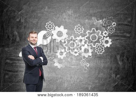 Confident young businessman with a beard is standing with his arms crossed near a blackboard with a wrench and many cogs on it. Concept of teamwork