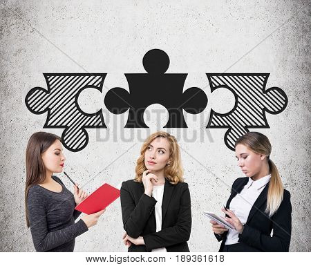 Three young businesswomen are standing near a concrete wall with three matching puzzle pieces above their head and brainstorming. Concept of a teamwork