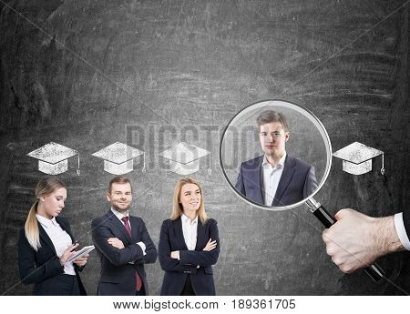 Row of business college graduates in suits. They are standing near a blackboard with graduation hats above their heads. Big boss s hand with a magnifying glass is picking the right candidate
