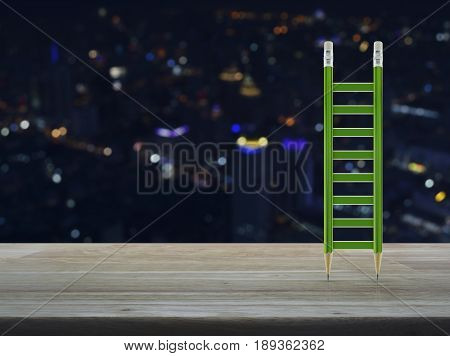 Green pencil ladder on wooden table over blur colorful night light city tower Business success concept