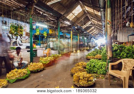 BANGALORE, INDIA - FEB 16, 2017: Market traders and buyers walk in motion blur in a storehouse with bananas on February 16, 2017. With popul. 8.52 million Bangalore is the 3rd most populous indian city