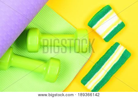 Dumbbells On Green And Purple Mat For Yoga And Sweatband