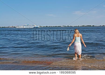 Volgograd Russia - May 08 2012: Blond woman paddling her bare feet during a flood in the background of the Volga River with a boat