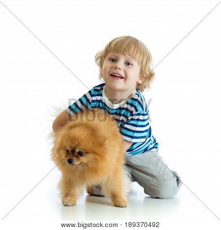 Child boy hugging dog spitz, isolated on white background