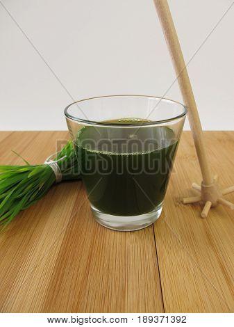 Drinking glass of homemade green wheatgrass juice