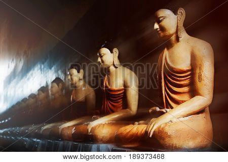 Buddha statues in the cave temple in the rays of light. Sri Lanka. Tangalle. Mulkirigala Raja Maha Viharaya Temple.