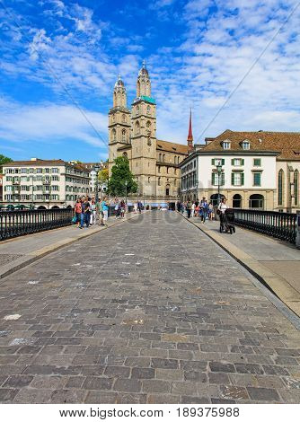 Zurich, Switzerland - 26 May, 2016: view along the Munsterbruecke bridge towards the Grossmunster cathedral, pedestrians on the bridge. Munsterbrucke is a pedestrian and road bridge over the Limmat river in the city of Zurich, Switzerland.