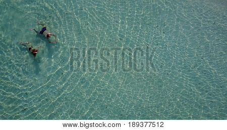 Aerial flying drone view of Maldives white sandy beach 2 people young couple man woman swimming splashing underwater on sunny tropical paradise island with aqua blue sky sea water ocean