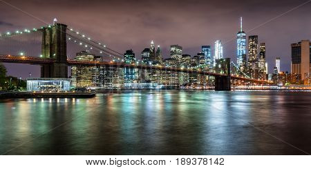 Panoramic view of the Brooklyn Bridge with Financial District skyscrapers at twilight and light clouds. Lower Manhattan New York City
