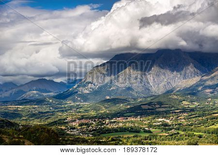 Saint Bonnet en Champsaur and the Petit Chaillol mountain peak in the clouds. Summer in the Southern French Alps. Hautes-Alpes PACA Region Champsaur France